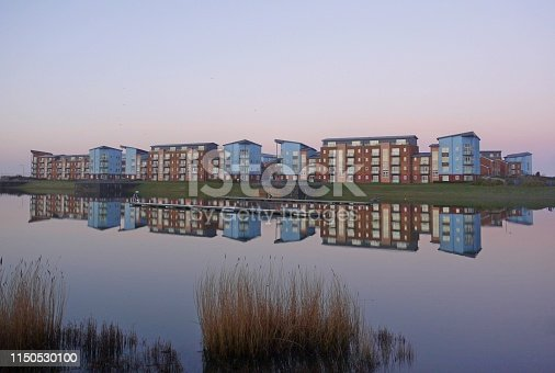 block of modern lakeside apartments photographed at twilight with reflection