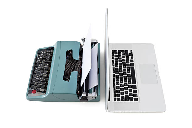a modern laptop against a vintage typewriter - historic vs new stock photos and pictures
