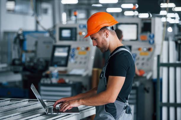 Moderner Laptop. Tippen auf der Tastatur. Industriearbeiter in der Fabrik. Junger Techniker mit orangefarbenem Harthut – Foto