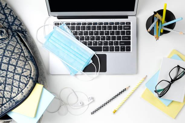 白色桌子上配有背包和文具的現代筆記型電腦 - 虛擬辦公室 個照片及圖片檔