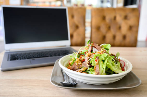 Modern laptop with spicy pork salad on table stock photo