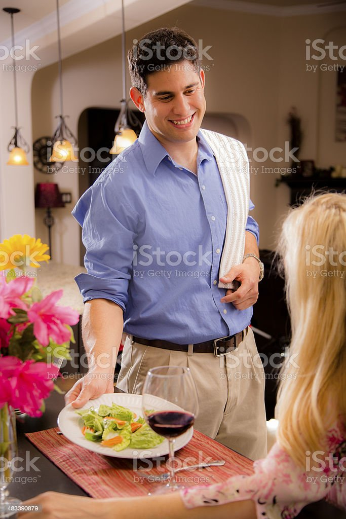 Modern, Latin man makes dinner for wife at home. royalty-free stock photo
