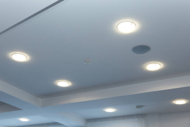 modern layered ceiling with embedded lights and stretched ceiling inlay, lights on - потолок стоковые фото и изображения