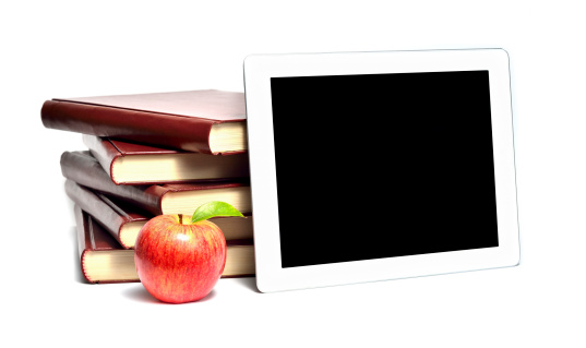 Stack of books with digital tablet and apple on top.