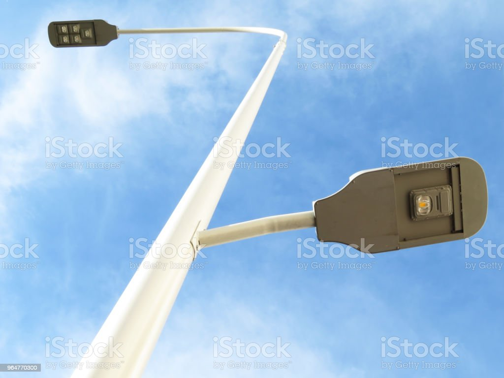 Modern LED street lamp post on blue cloudy sky background royalty-free stock photo