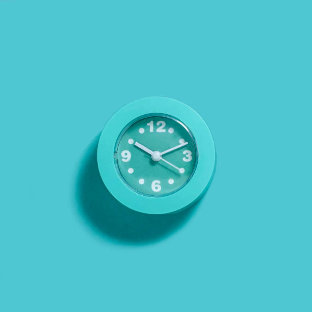 Modern light blue alarm clock on blue background stock photo