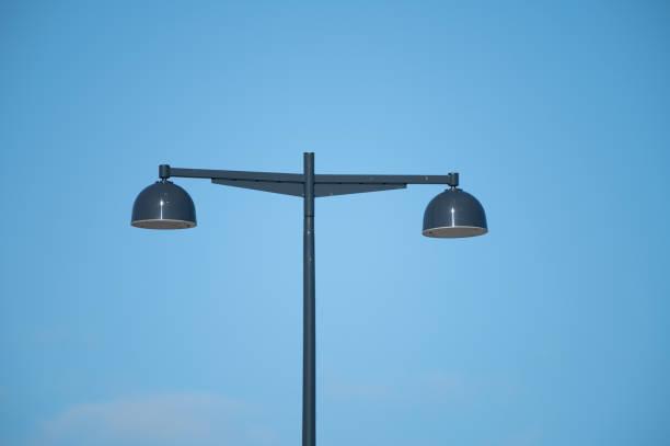 A modern light pole against blue sky stock photo