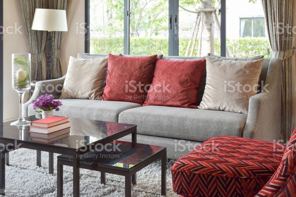 modern living room design with red pillows on sofa and decorative table lamp stock photo