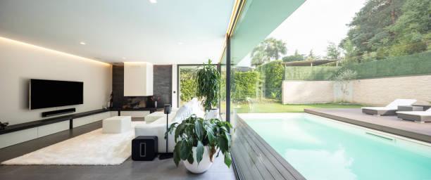 Modernes Wohnzimmer mit Blick auf den Garten und den Swimmingpool. – Foto