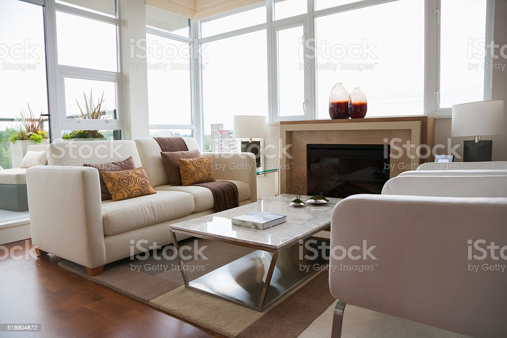 Modern living room surrounded with large picture windows stock photo