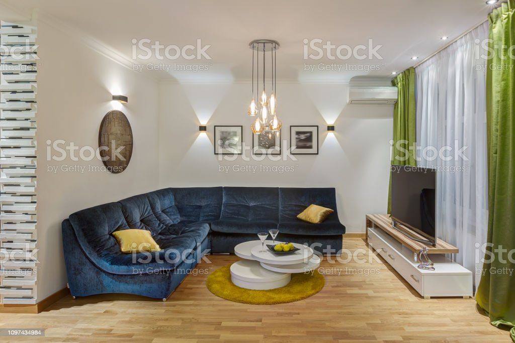 Modern Living Room With Big Dark Blue Sofa With Yellow Pillows Glasses Table In Center Of Room Creative Picture On Wall Comfortable Place With Tv Interior In Green White And Dark Blue