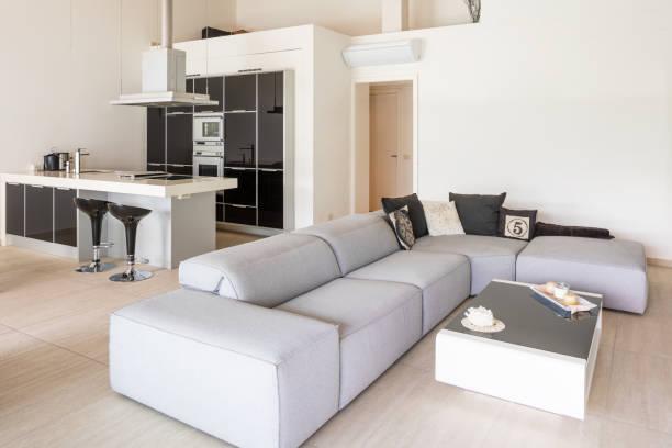 Modernes Wohnzimmer mit niedrigem Sofa und weißer und schwarzer Küche mit Insel und Hockern – Foto