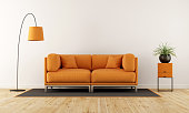 istock Modern living room with orange couch 637876746