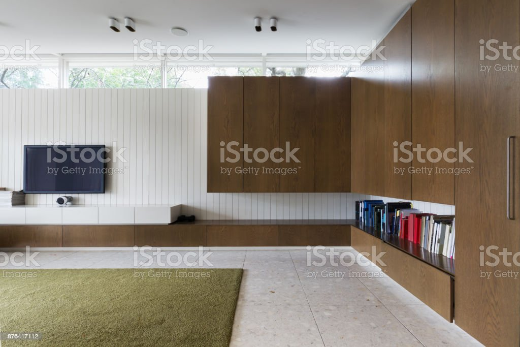 Modern Living Room With Walnut Built In Cabinets And Tv Stock
