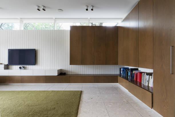 modernes wohnzimmer mit walnuss eingebaute schränke und tv - oliven wohnzimmer stock-fotos und bilder