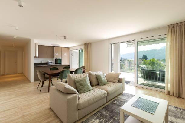 Modernes Wohnzimmer mit Holztisch, Samtstuhl und großem Sofa – Foto