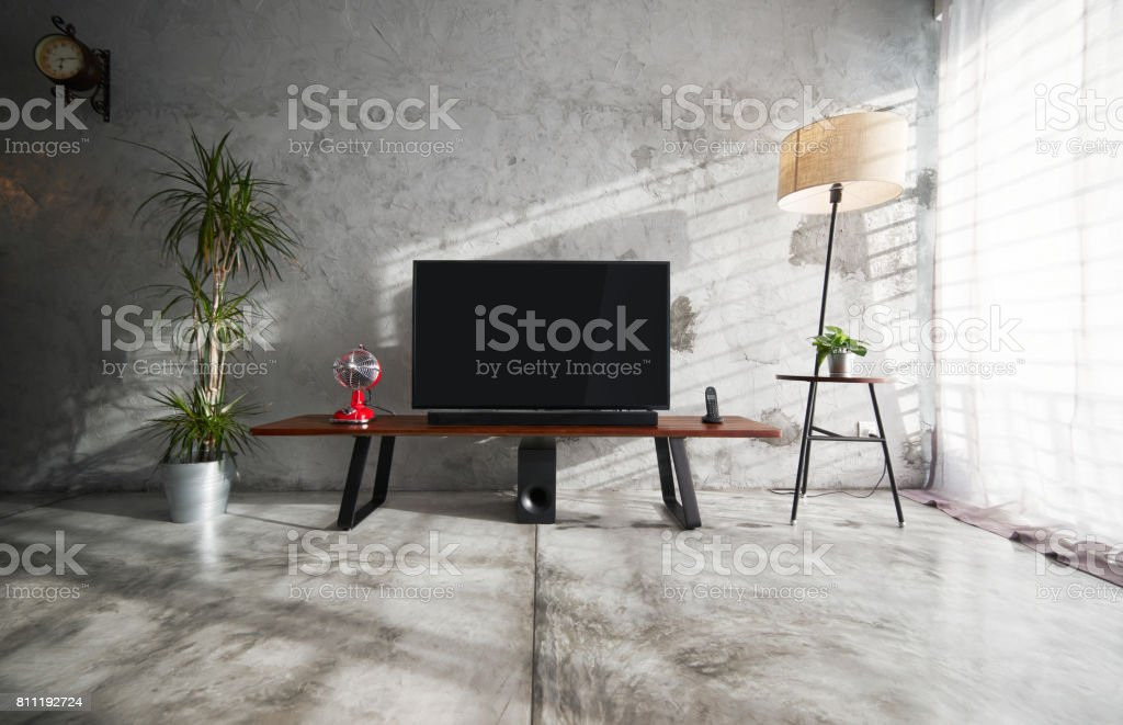 Modern living-room interior with TV in a loft style with wooden TV deck and concrete walls and floor . There are vintage fan and clock ,lamps and green plant to decorate . stock photo