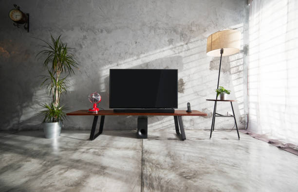 modern living-room interior with tv in a loft style with wooden tv deck and concrete walls and floor . there are vintage fan and clock ,lamps and green plant to decorate . - cement floor stock photos and pictures