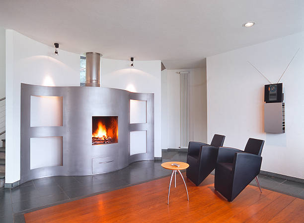 Modern living-room with curved fireplace and black leather chairs stock photo
