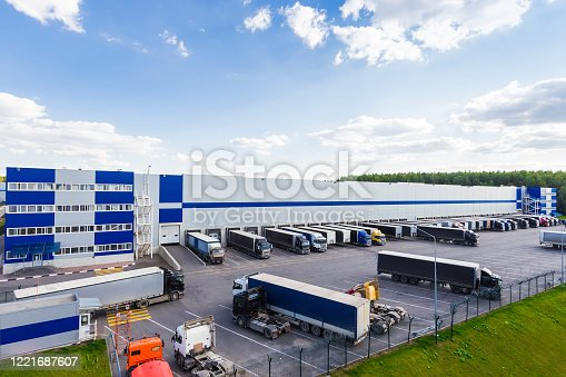 Modern warehouse during business hours with a lot of different cargo truck
