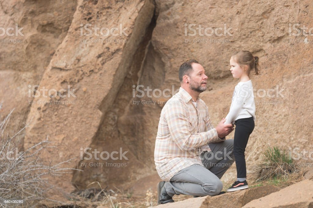 Modern looking dad has a serious talk with his young daughter about obedience royalty-free stock photo