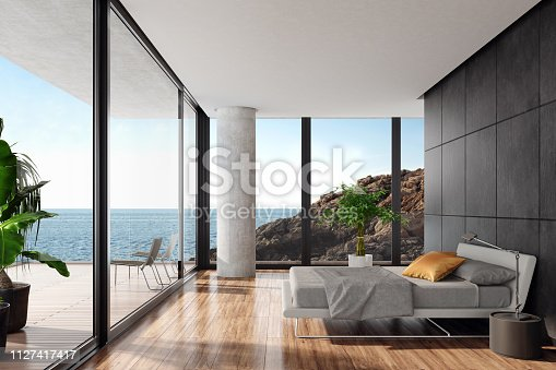 Luxurious minimalist bedroom in a seaside villa with big panoramic windows and ocean view. White textile king size bed with white metal construction in front of  black wall with natural stone large tiles. Round modern gray nightstand with a modern metal lamp next to the bed. Wooden varnished floor. Big terrace with an ocean view and glass fence with green plants. Summer daylight scene. Background is my own photo.