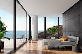 Luxurious minimalist bedroom in a seaside villa with big panoramic windows\nand ocean view. White textile king size bed with white metal construction in front of \nblack wall with natural stone large tiles. Round modern gray nightstand with a\nmodern metal lamp next to the bed. Wooden varnished floor. Big terrace with an\nocean view and glass fence with green plants. Summer daylight scene.\nBackground is my own photo.