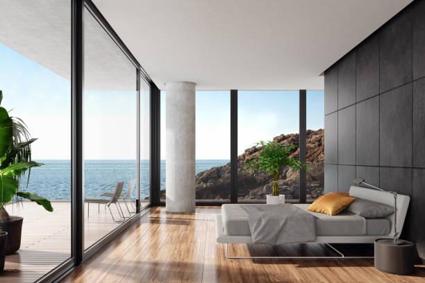 黒の石壁が備わるシーサイドヴィラでモダンな豪華なベッドルーム - 豪華 ストックフォトと画像