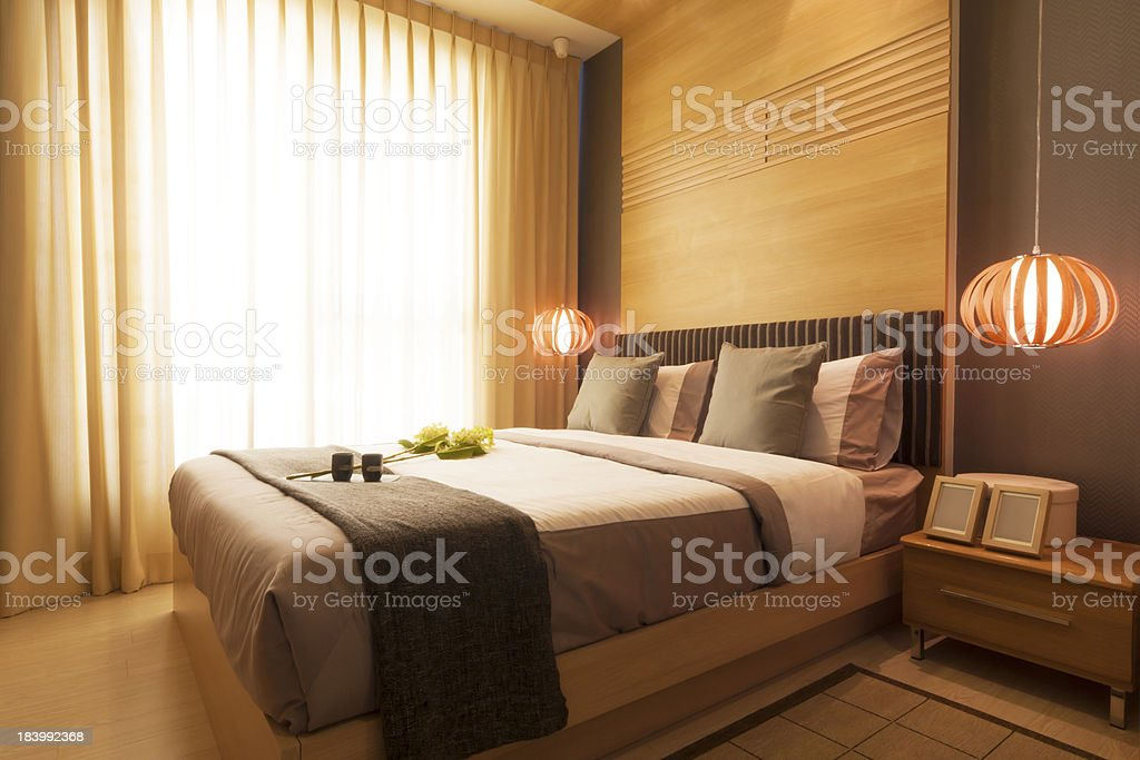 Modern luxurious bedroom with a king size bed and two lights royalty-free stock photo