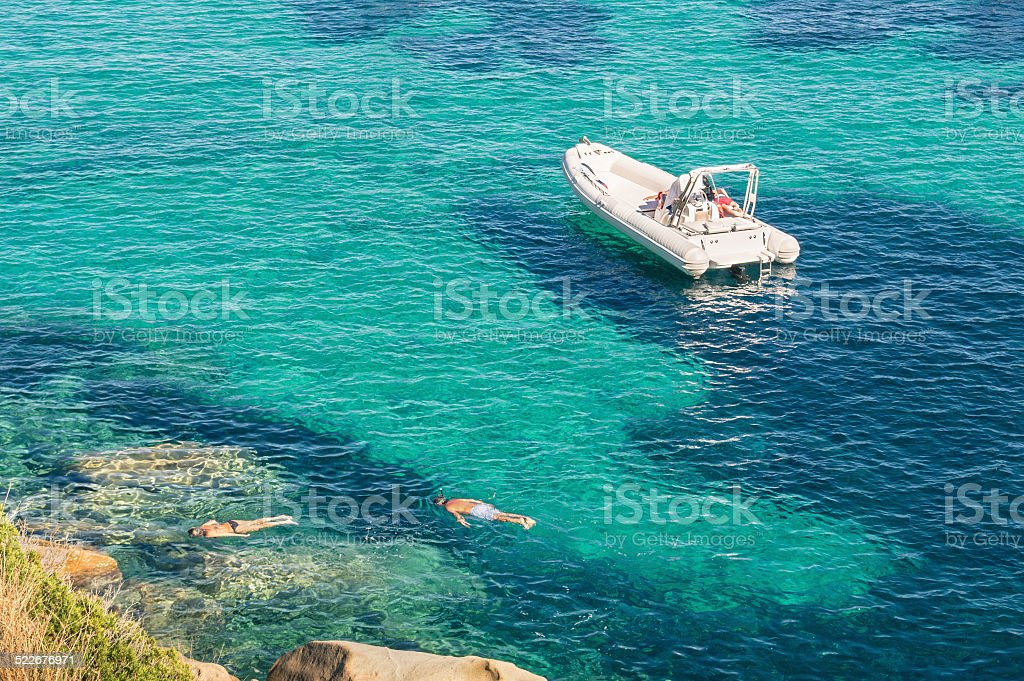 Modern luxury dinghy on turquoise sea with clear blue water stock photo
