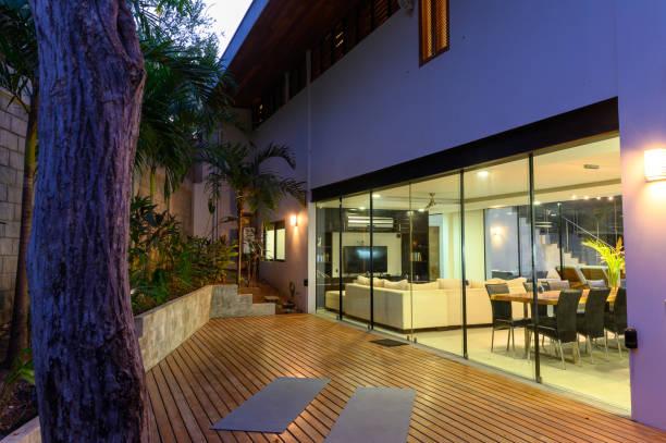 modernes luxushaus in der dämmerung - outdoor esszimmer stock-fotos und bilder