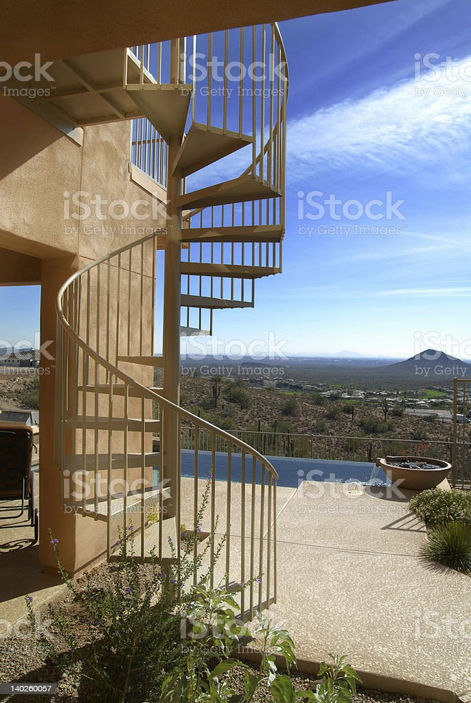 Modern Luxury Home with Spiral Stairway on Patio royalty-free stock photo