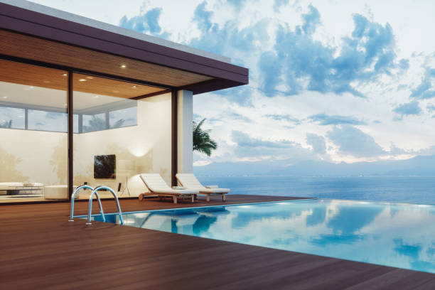 Modern Luxury House With Infinity Pool At Dawn Modern luxury villa exterior with infinity pool and beautiful ocean view at dawn. holiday villa stock pictures, royalty-free photos & images
