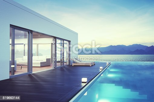 Minimalist modern villa exterior with infinity pool and beautiful ocean view at dawn.