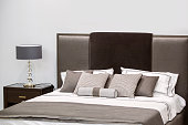 Modern luxury interior of the bedroom. Design of a room in a hotel with a bed and original table lamp