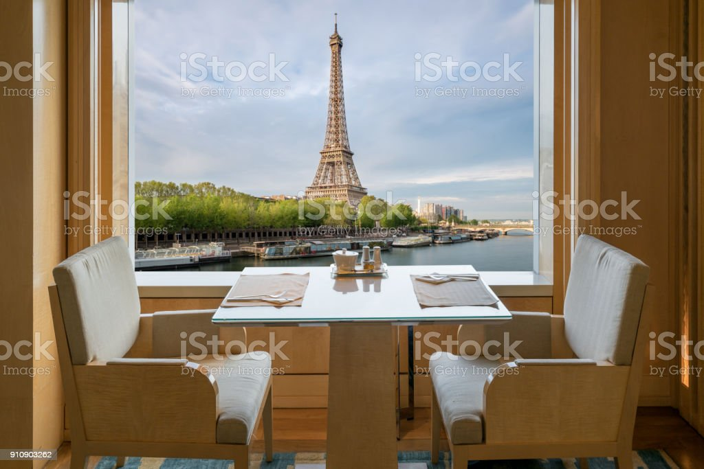 Modern luxury restaurant interior with romantic sence Eiffel Tower and Seine river view in Paris, France. Dinning table in restaurant at Paris, France. stock photo