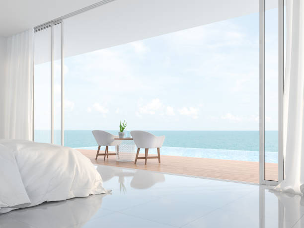 Modern luxury white bedroom with sea view 3d render Modern luxury white bedroom 3d render.There is a minimalistic building with white beds and chairs. There is a large open sliding door overlooking the infinity pool and sea view. infinity pool stock pictures, royalty-free photos & images