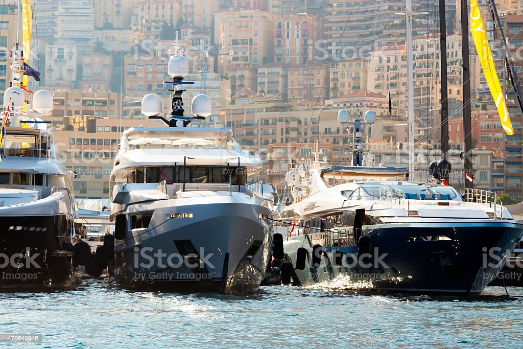 Modern luxury yachts in Monaco marina with apartment buildings behind stock photo