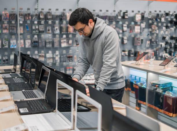 moderne männliche kunden laptop in der computer-shop wählen - freizeitelektronik stock-fotos und bilder