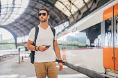One man, handsome young man with backpack on train station, using smart phone.