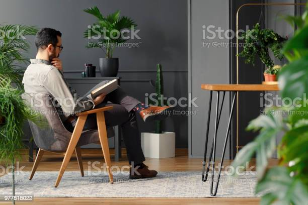 Modern man reading book while sitting in grey armchair in trendy picture id977818022?b=1&k=6&m=977818022&s=612x612&h=w9hpizzte9yoeg 5fla9ulbp e ockr ed8kgihe2sy=