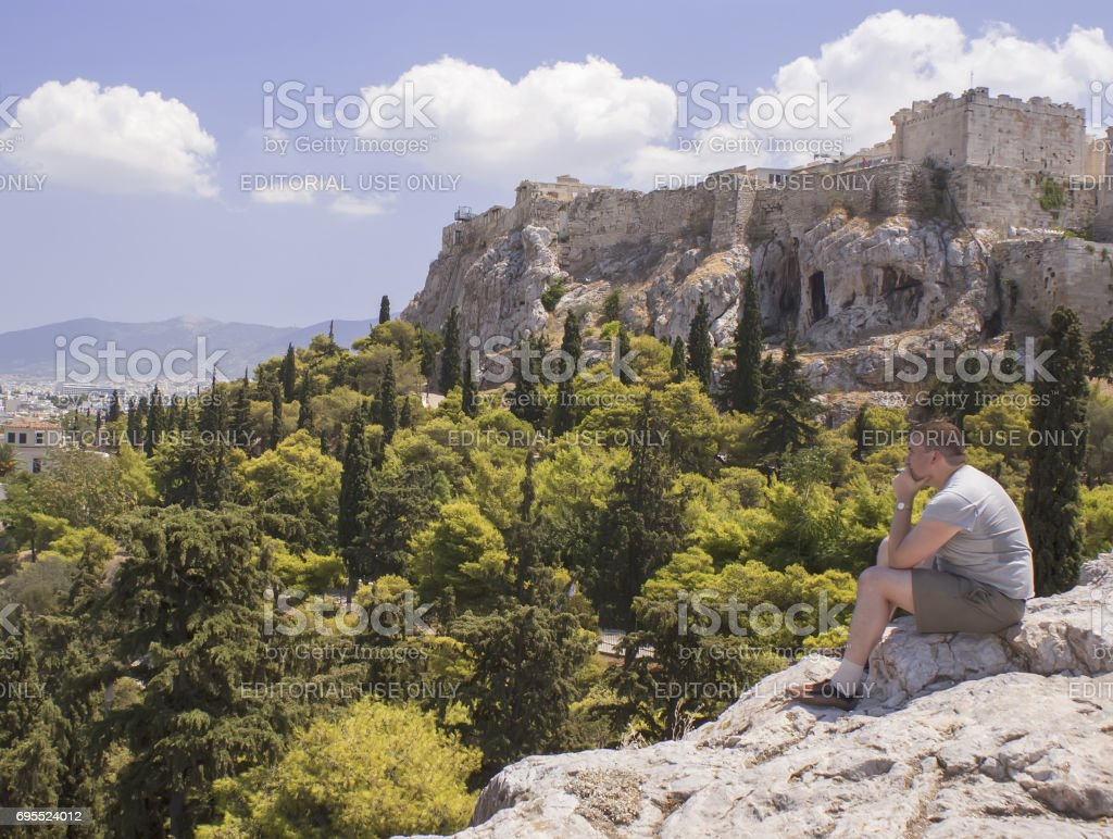 Modern man sits at the foot of the Ancient Acropolis in Greece in Athens and thinking about the great history'n stock photo