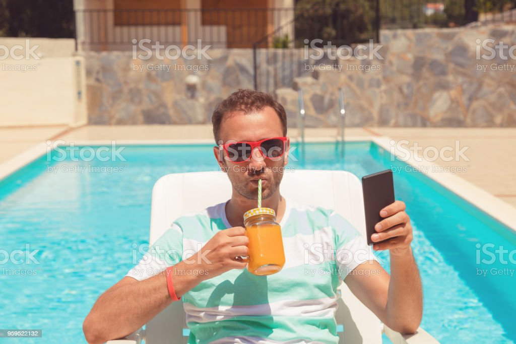 Modern man using cellphone while drinking juice on the pool. stock photo