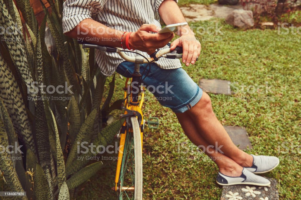 Modern man using cellphone while sitting on the grass with old bicycle. stock photo