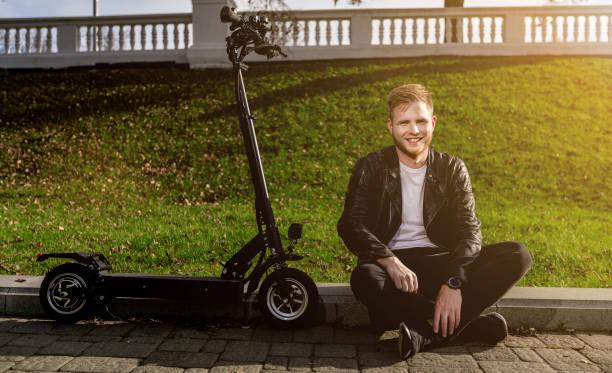 Moderner Mann mit technologischem Elektro-Kick-Scooter. Konzept mit Kopierplatz an der Straße bei gutem Wetter. Er entspannt in der Nähe von kickscooter – Foto