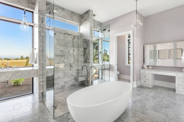 modern master bathroom interior in new luxury home with glass shower doors, and luxurious soakingbathtub