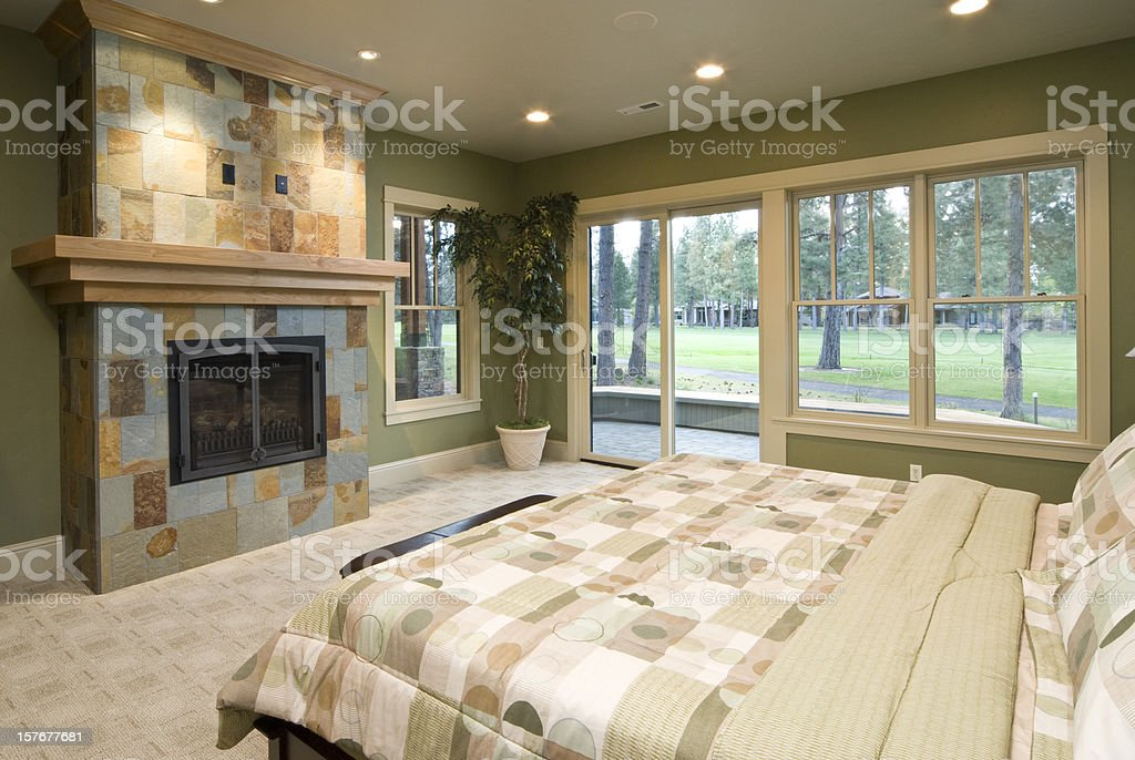 Modern master bedroom with tiled fireplace stock photo