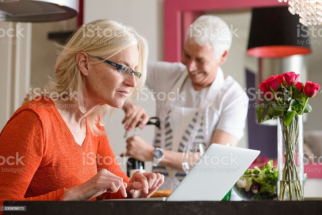 Modern Mature Couple Preparing Food and Working on Laptop stock photo