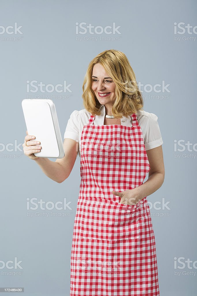 Modern mature housewife using digital tablet royalty-free stock photo
