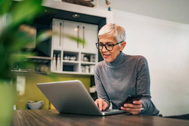Mujer madura moderna usando computadora portátil y teléfono inteligente en casa, retrato. - foto de stock